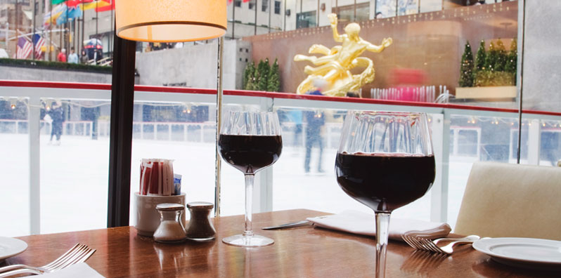 Wine glasses on table overlooking the ice rink