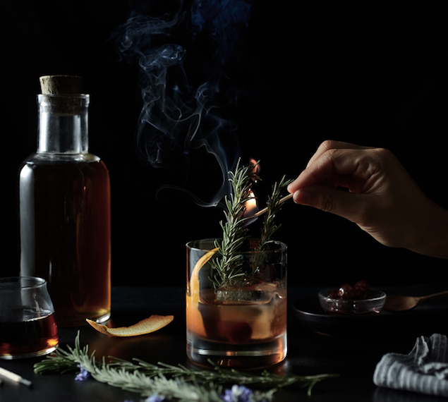 setting rosemary spice on fire in a cocktail